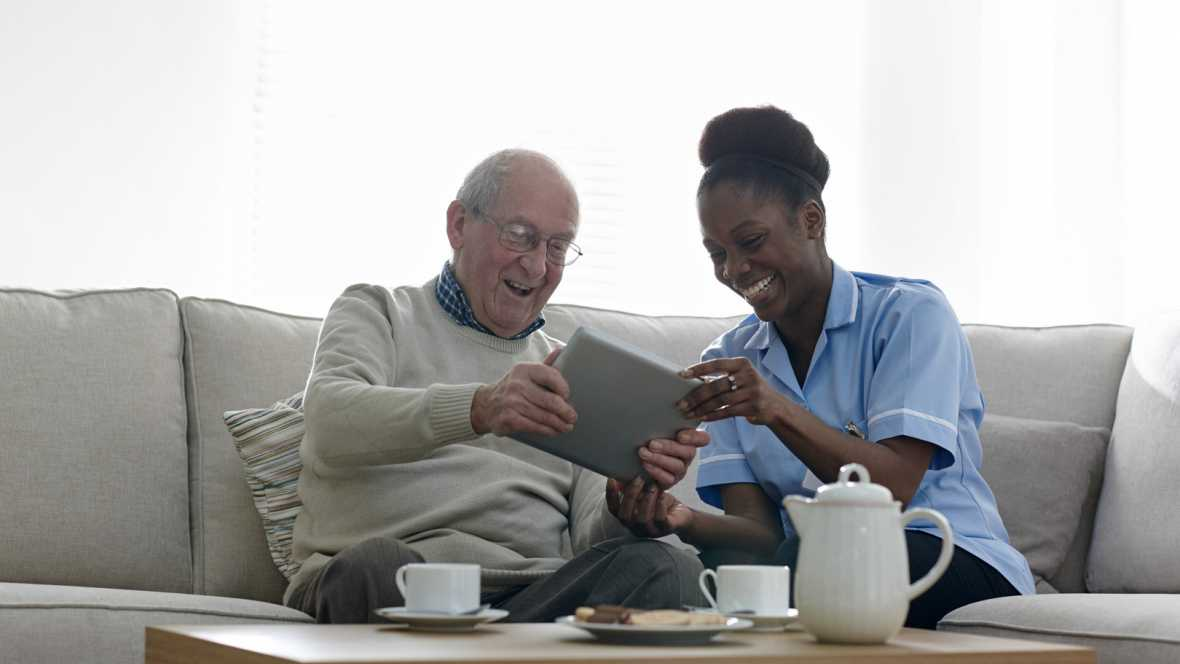 Happy Patient and Nurse looking at uniti Mobile